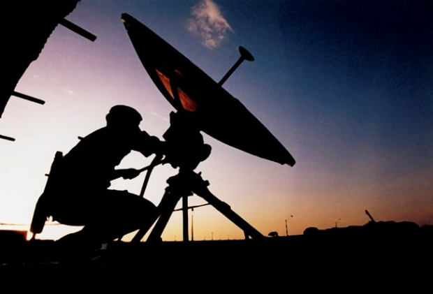 A soldier adjusts a satellite dish.